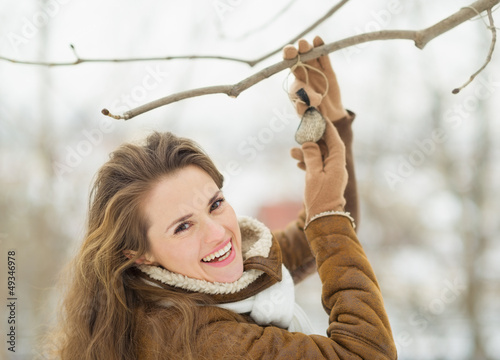 Fotografía  Smiling young woman hanging bird feeder on tree in winter park