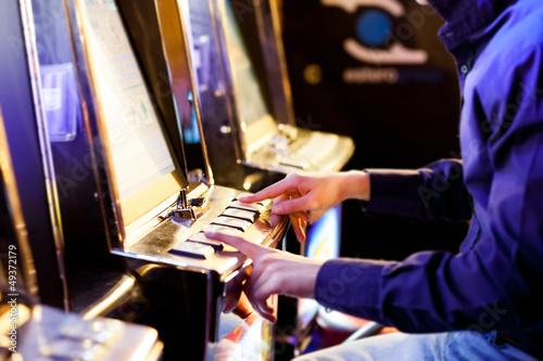 Man using an electronic slot machine плакат