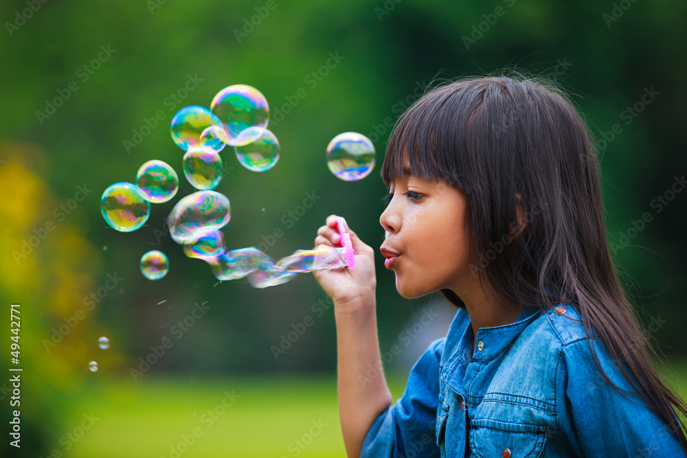 Fototapety, obrazy: Asian little girl is blowing a soap bubbles
