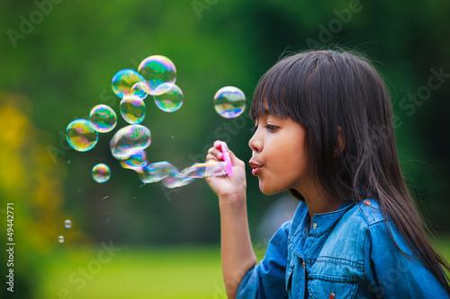 Asian little girl is blowing a soap bubbles Canvas Print