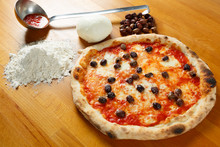 Italian Pizza, Ingredients In The Background On A Wood Table