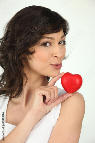 Photo a brunette woman and a little red plastic heart