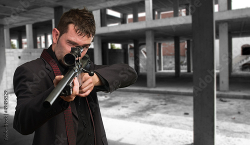 Man in suit pointing with a rifle Canvas Print
