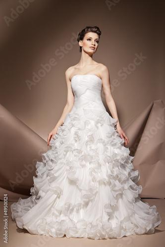 Foto  The beautiful young woman in a wedding dress