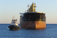Cargo Ship With Tug Boat Assis...