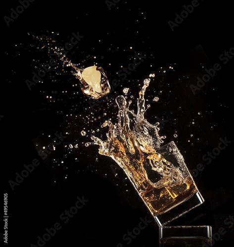 Glass of whiskey with splash, isolated on black background Fototapete