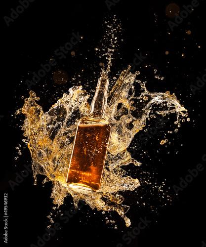 Photo Concept of liquor splashing around bottle on black background
