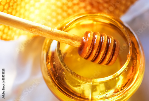 Foto auf AluDibond Bienen Honey dipper with bee honeycomb
