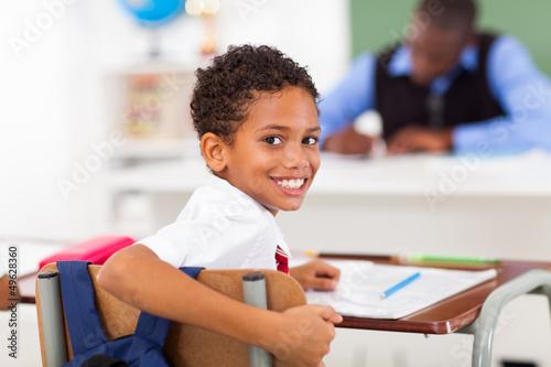 Photo  cute elementary schoolboy looking back in classroom