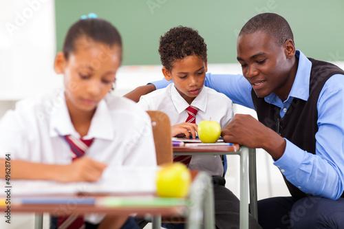 Canvas Print elementary school teacher helping student in classroom