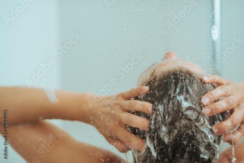 Fotografie, Obraz  Closeup on young woman washing head with shampoo