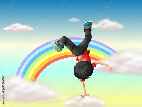 In de dag Regenboog A boy performing a break dance along the rainbow