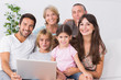 Happy family on couch using laptop