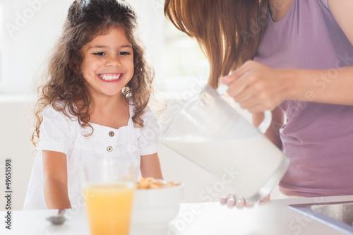 Fototapeta Mother putting milk in the cereal of his daughter obraz