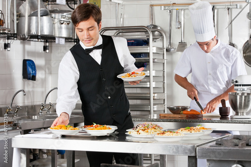 Fotobehang Restaurant Waiter And Chef Working In Commercial Kitchen
