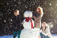 Three Girls Building A Snowman