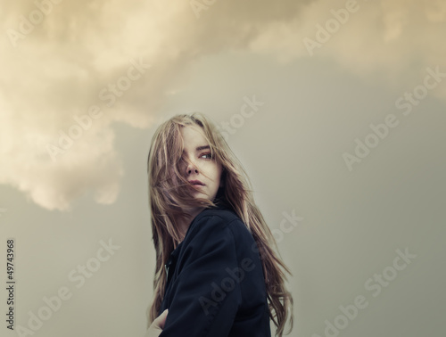 Fotografering  beautiful young woman on a background of clouds