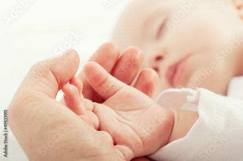 hand the sleeping baby in the hand of mother Poster