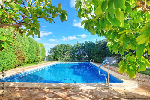 Foto op Plexiglas Groene Outdoor swimming pool with blue water near the garden.