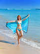 The young attractive woman on a beach with a scarf in hands..