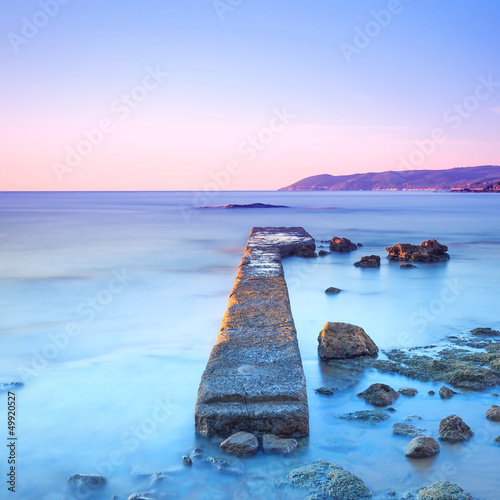Concrete pier or jetty and rocks on a blue sea. Hills on backgro