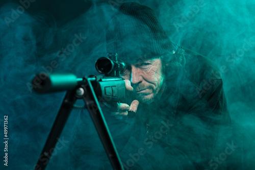 Fotografía  Sniper with beard in black holding gun. Studio shot.