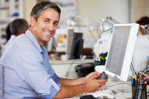 Fototapety, obrazy: Man Using Mobile Phone At Desk In Busy Creative Office