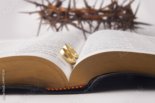 Marriage rings on holy bible and crown of thorns