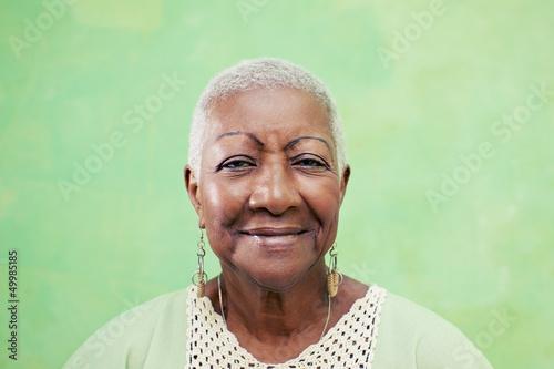 Fotografie, Obraz  Portrait of senior black woman smiling at camera on green backgr