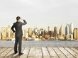 Businessman standing on pier and modern city