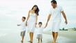Latin American family walking on beach dressed in white