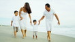 Hispanic family walking together by ocean dressed in white