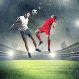 Dwóch zawodników skaczących do piłki