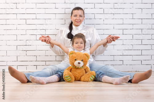 Mother, daughter and toy sitting against the wall Poster