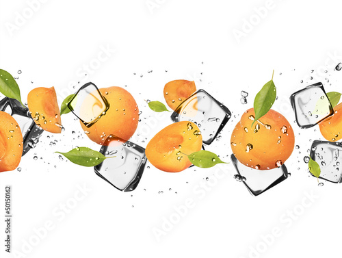 Foto auf Leinwand In dem Eis Apricots with ice cubes, isolated on white background