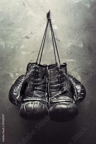фотография old boxing gloves hang on nail