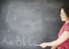 Japanese Teacher Writing On Blackboard