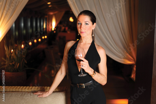 Beautiful Woman In A Black Dress With A Glass Of Wine On A Dark