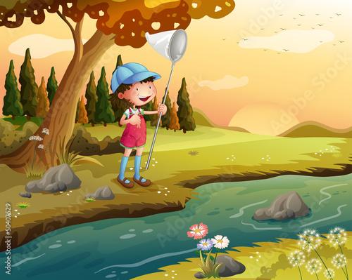 In de dag Indiërs A girl holding a net along the river