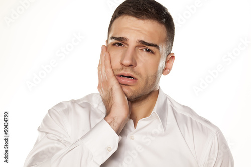 Fotografia  a young man with a toothache on white background