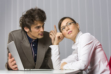 Businessman Trying To Convince His Pensive Businesswoman Partner