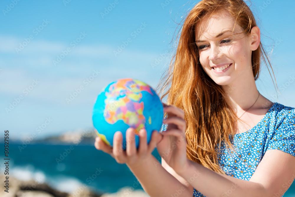 Fototapeta junge frau mit globus am meer