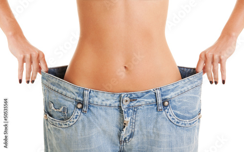 Fotografía  Woman shows her weight loss by wearing an old jeans, isolated on