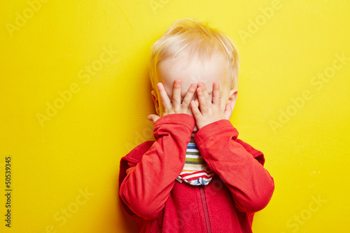 фотография  Kleines Kind hält sich die Augen zu