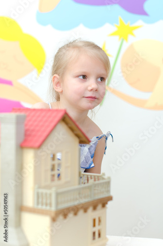Photo  Little girl playing with dollhouse