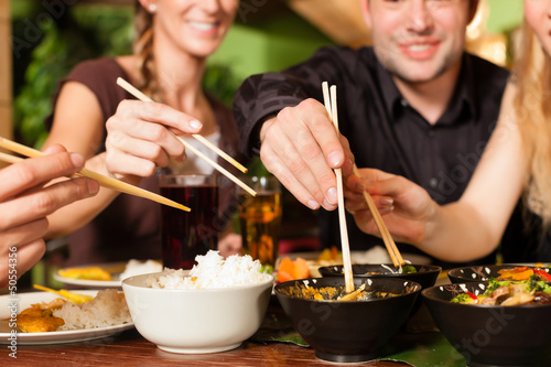 Photo  Young people eating in Thai restaurant