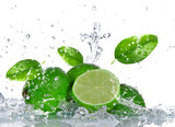 Limes with water splash isolated on white