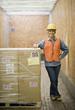 Hispanic warehouse worker next to shipment