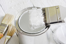 Paint Brush And Can On White Planks