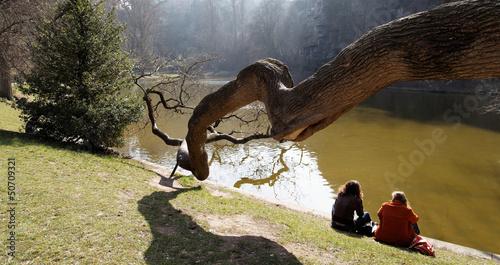 Deux femmes de dos au bord de l eau avec branche